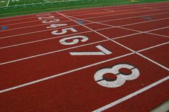 Lanes on running track. Numbered lanes at start of athletic running track with lane eight in foreground Royalty Free Stock Photos
