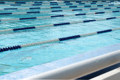 Lanes of swimming pool over light blue transparent  water. Royalty Free Stock Photos