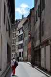 A narrow laneway on a sunny day in Strasbourg, France. A person walking through a narrow alley with half timbered houses running along both sides on a sunny day Stock Photography