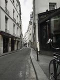 A quiet narrow laneway in Paris. Photo of a quiet narrow alley in Paris with a bicycle in the forefront and a person in the distance. The photo is in in muted stock photography