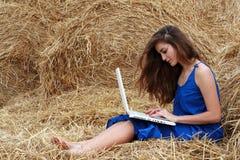 Lang-behaartes Mädchen, das auf Heu mit Laptop sitzt Lizenzfreies Stockfoto