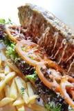 Lang brood met groente en gebraden gerechten Stock Afbeeldingen