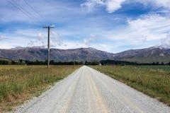 Lang gerade Straße zum Gebirgszug lizenzfreie stockfotografie