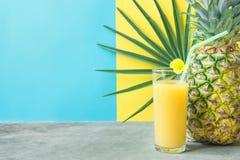 Lang Glas met vers Gedrukte Ananas Oranje Kokosnoot Juice Straw en Kleine Bloem Rond Palmblad op Blauwe Gele Achtergrond Stock Afbeelding