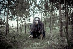 Lang haarmeisje met enge make-up in het bos Stock Afbeeldingen