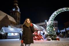 Lang haarmeisje op Europese Kerstmismarkt Jonge vrouw die van het Seizoen van de de Wintervakantie genieten Vage Lichtenachtergro Stock Foto's