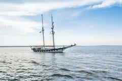 Lang schip op blauw water Stock Fotografie