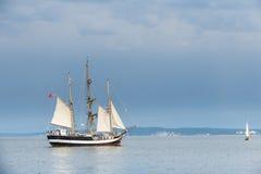 Lang schip op blauw water tegen stormachtige wolken. Stock Afbeelding