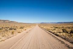 Lang trostloser Schotterweg in te Utah-Wüste Lizenzfreie Stockfotografie