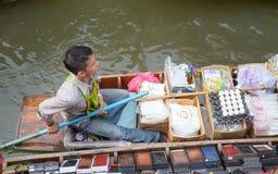 Langa lokal man med ett fartyg i Thailand som svävar marknaden Damnoen Saduak nära Bangkok, Bangko arkivbild