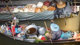 Langa lokala kvinnor med ett fartyg i Thailand som svävar marknaden Damnoen Saduak nära Bangkok, Bangko arkivbild