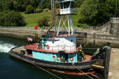 Langarebogserbåten med högstämda wheelhousepushes rusar in i lås Royaltyfria Bilder