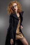 langbeiniges Mädchen mit dem herrlichen Haar und den schönen Augen in einem verlockenden kurzen goldenen Kleid und in einem graue Stockbild