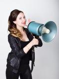Langbenig mooi meisje in zwart nauwsluitend broeken en jasje, schreeuwt zij in een megafoon Public relations stock foto's