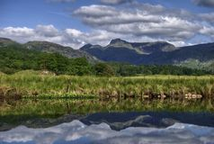 Langdale Pikes reflected in river Stock Photo