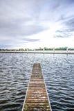 Lange Anlegestelle auf einem ruhigen Wasser durch eine Bucht mit Wolken auf einem Himmel, Polen Lizenzfreie Stockbilder