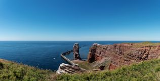 Lange Anna sea stack rock on Heligoland island against blue sea and clear sky. High angle view of Lange Anna sea stack rock on Heligoland island against blue sea Royalty Free Stock Photos