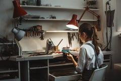 Lange Arbeitsstunden Hintere Ansicht des jungen weiblichen Juweliers, der neues Produkt an ihrer Schmuckwerkstatt macht stockbilder