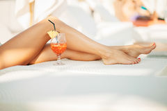 Lange Beine und tropisches Cocktail Lizenzfreie Stockbilder