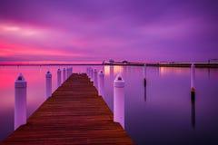 Lange Belichtung bei Sonnenuntergang eines Piers und der Chesapeake Bay-Brücke, Stockfotos