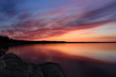 Lange Belichtung des vibrierenden Sonnenuntergangs über einem See Stockbild