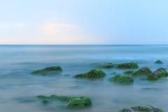 Lange Belichtung geschossen vom Meer und von den Felsen mit Meerespflanzen Stockbild