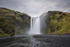 Lange Belichtung Skogafoss-Wasserfalls an einem bewölkten Tag Lizenzfreie Stockfotos