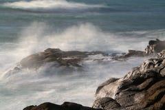 Lange Belichtung von den Wellen, die in die Felsen zusammenstoßen lizenzfreie stockfotos
