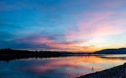 Lange Belichtungslandschaftsphotographie des Sonnenuntergangs nachdenkend über Wasseroberfläche Stockbilder