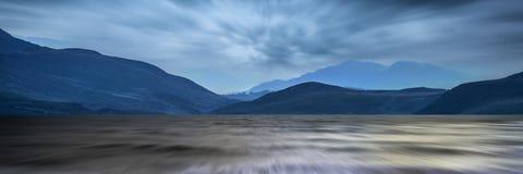 Lange Belichtungspanoramalandschaft des stürmischen Himmels und der Berge ov Stockfoto