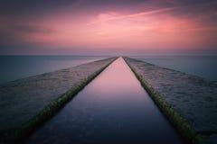 Lange Belichtungssonnenuntergangweitwinkelansicht des Meeres von einem Pier Lizenzfreie Stockfotografie