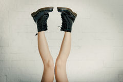 Lange benen in grote zwarte schoenen Stock Afbeelding