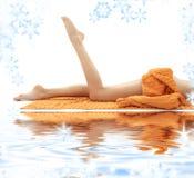 Lange benen van meisje met oranje handdoek op wit zand royalty-vrije stock foto