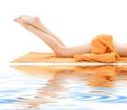 Lange benen van ontspannen dame met oranje handdoek stock afbeelding