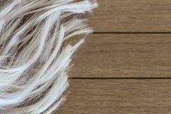 Lange blonde vrouwelijke pruik op een houten achtergrond royalty-vrije stock fotografie