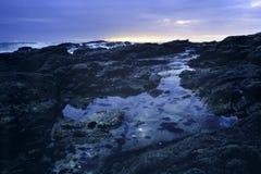 Lange blootstelling in een Portugees rotsachtig strand bij schemer stock fotografie