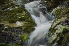 Lange blootstellingsclose-up van kleine watervallen tussen behandelde rotsen stock afbeelding