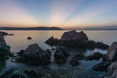 Lange blootstellingsfoto die van water door rotsen op de mooie zonsondergang gaan, zon die achter eiland gaan stock foto