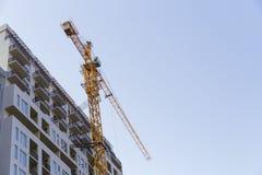 Lange bouwkraan, bouw van een woonwolkenkrabber stock foto