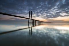 Lange Brücke über dem Tajo in Lissabon an der Dämmerung Stockbild
