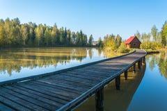 Lange Brücke, die zum Haus auf einer kleinen Insel geht Lizenzfreie Stockbilder