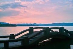 Lange brug door het Meer van het Westen van China bij Zonsondergang stock foto's