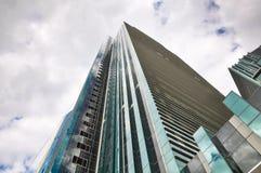 Lange bureauwolkenkrabber op een bewolkte hemel als achtergrond Royalty-vrije Stock Afbeeldingen