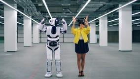 Lange cyborg herhaalt bewegingen na een meisje in VR-Glazen stock video