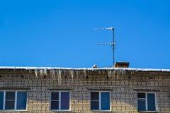 Lange Eiszapfen und Schneefall auf den Dachgesimsen des Hausdachs stockbilder