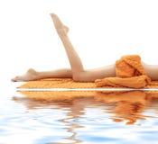 Lange Fahrwerkbeine des Mädchens mit orange Tuch auf weißem Sand Stockfoto