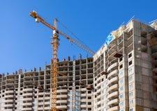 Lange flatgebouwen in aanbouw met kraan tegen a Stock Afbeeldingen
