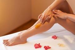 Lange Frauenfahrwerkbeine Frauensorgfalt über ihre Beine Zuckern von Behandlung Stockfoto