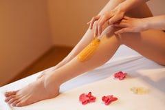 Lange Frauenfahrwerkbeine Frauensorgfalt über ihre Beine Zuckern von Behandlung Lizenzfreie Stockbilder