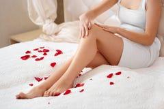 Lange Frauenfahrwerkbeine Schönheits-Sorgfalt über Beine Enthaarung Stockfoto